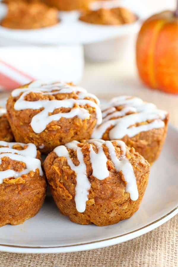 Healthy Pumpkin Muffins ona white plate with a pumpkin in the background.