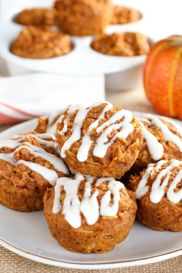 Plate of pumpkin muffins topped with white icing.