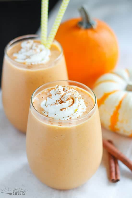 Pumpkin smoothie in a glass topped with whipped cream and cinnamon.