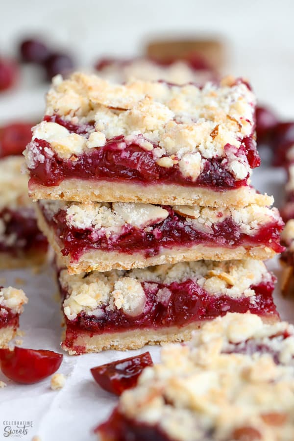Stack of three almond crumble bars filled with cherries.