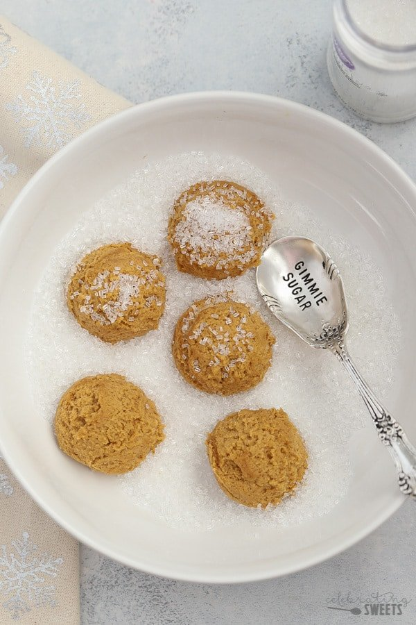 Ginger Molasses cookie dough balls in a bowl of sugar.