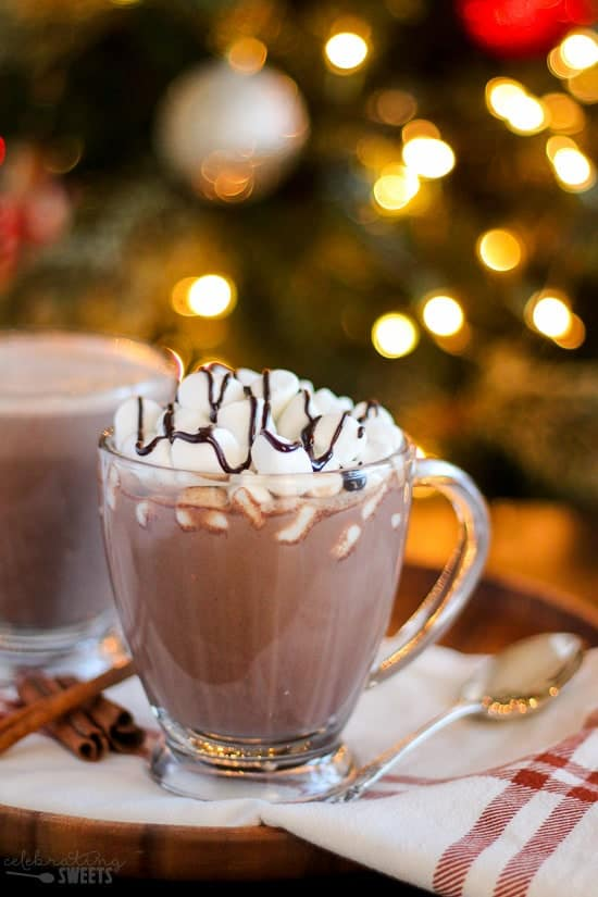 Glass of hot chocolate topped with marshmallows and a drizzle of chocolate sauce.
