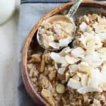 Bowl of oatmeal topped with coconut and almonds.