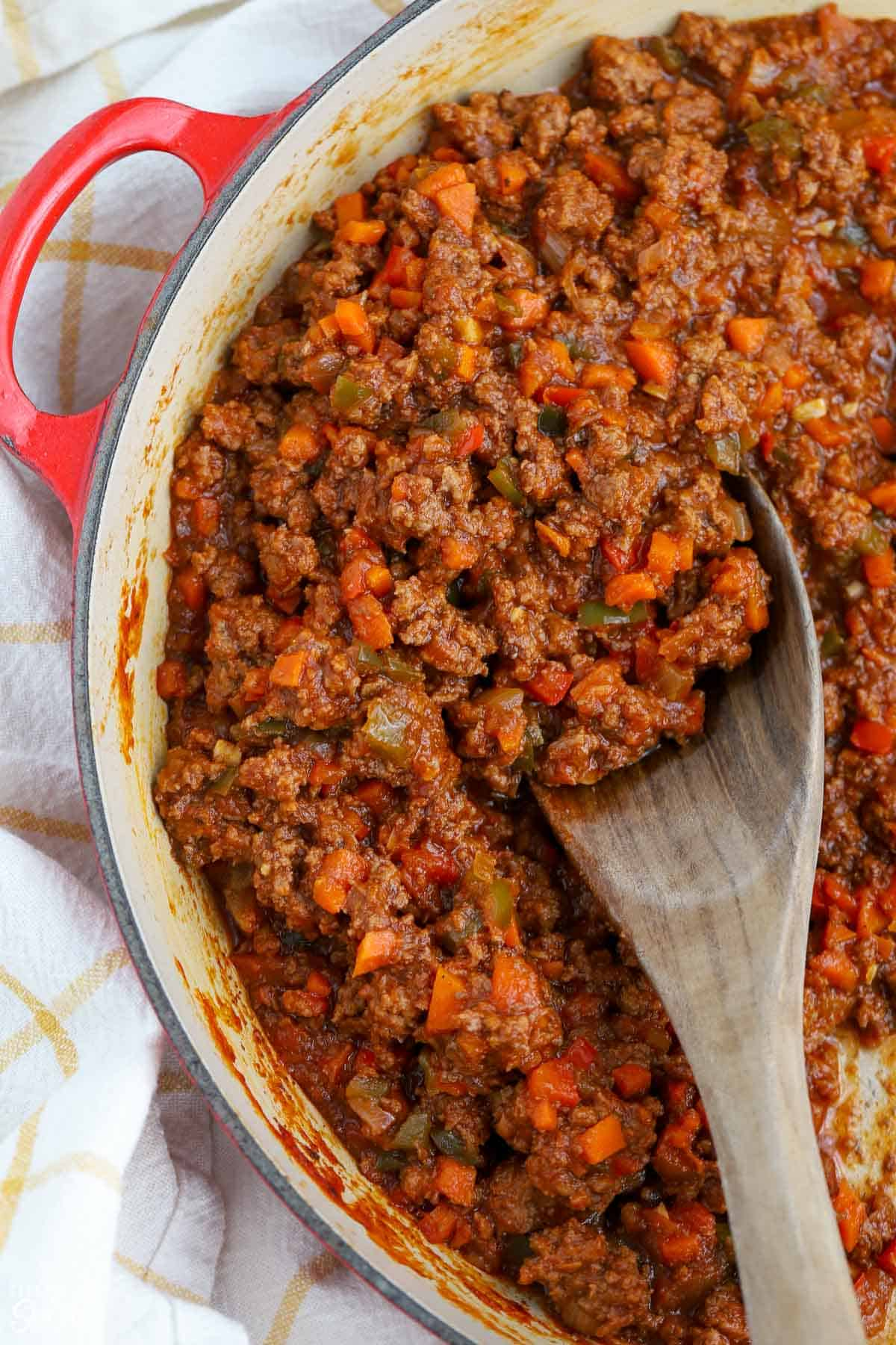 Sloppy joe meat in a pan with a wooden spoon