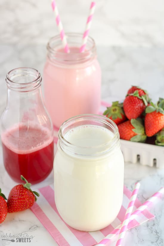 Ingredients for making strawberry milk: a glass of milk, strawberry syrup and fresh strawberries.