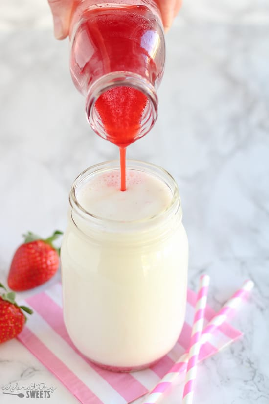 Red strawberry syrup being poured into a glass of milk.