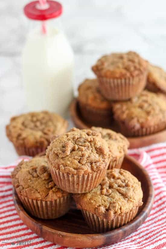 Peanut Butter Muffins in a wooden bowl with milk in the background.