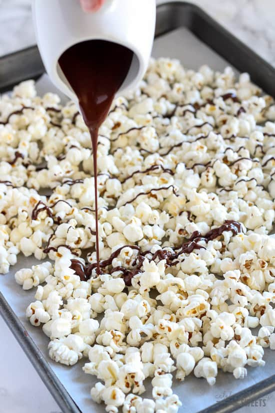 Tray of popcorn being drizzled with melted dark chocolate