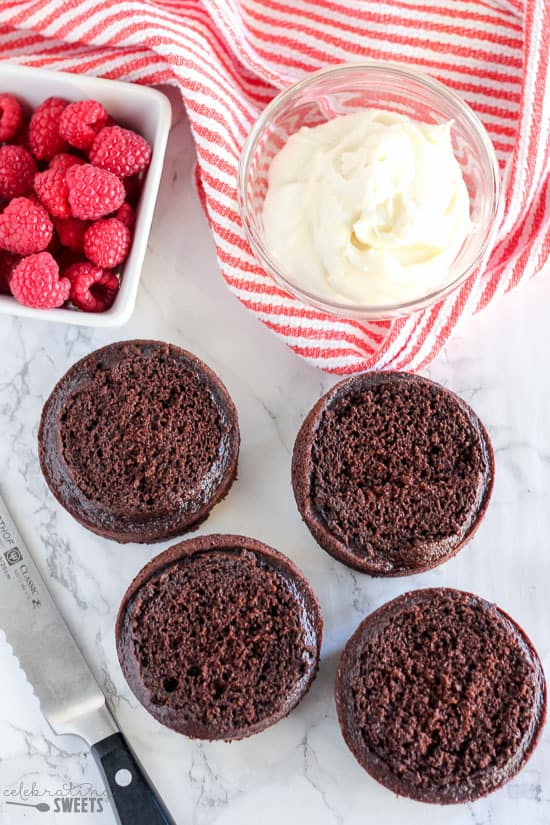 Four small chocolate cakes, white frosting in a bowl and raspberries in a white dish.