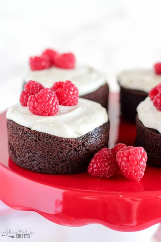 Small chocolate cake topped with white frosting and raspberries.
