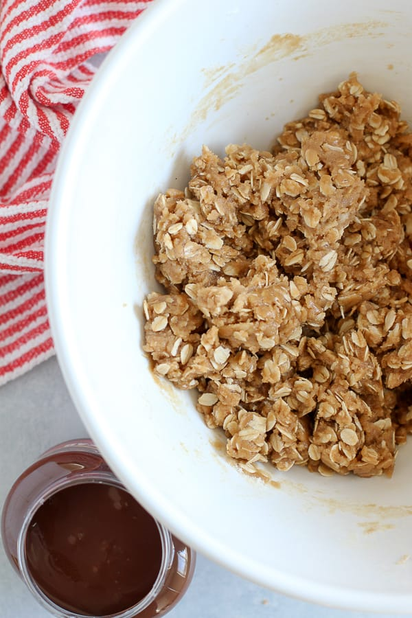 Oatmeal cookie dough in a large white bowl.