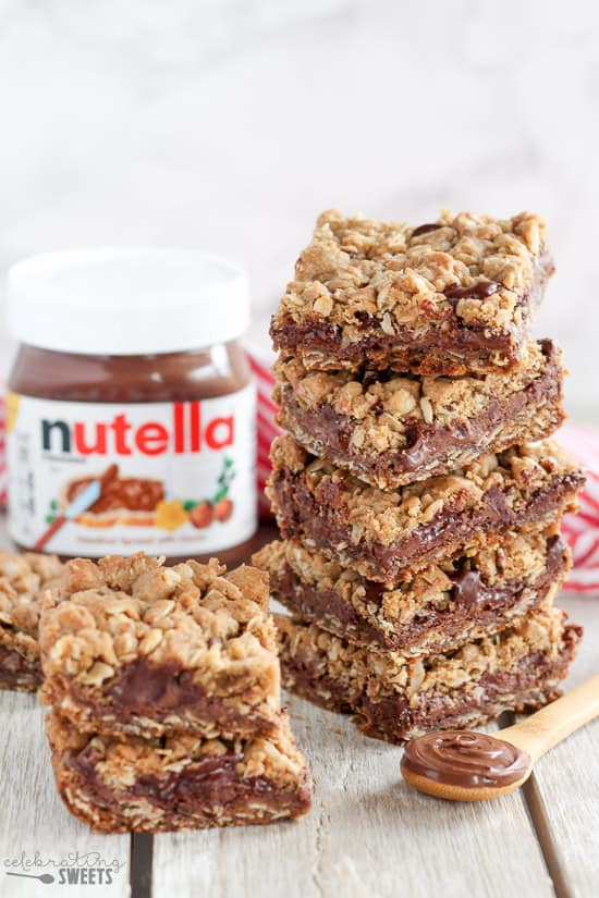 A stack of Nutella Dessert Bars with a container of Nutella in the background and a spoonful of Nutella on a wooden spoon.