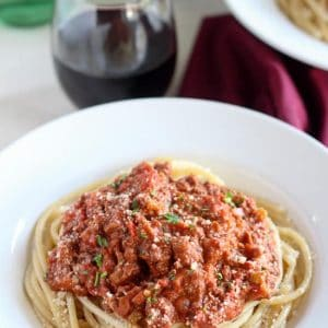 Bowl of pasta topped with meat sauce.