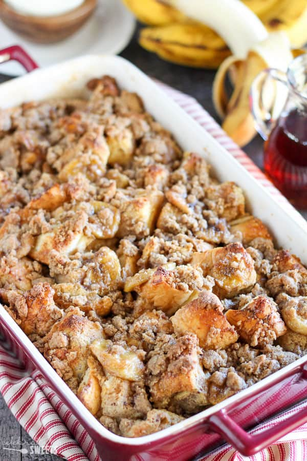 French toast casserole in a red baking dish with banana and syrup in the background.