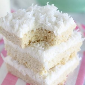 Stack of sugar cookie bars topped with coconut.