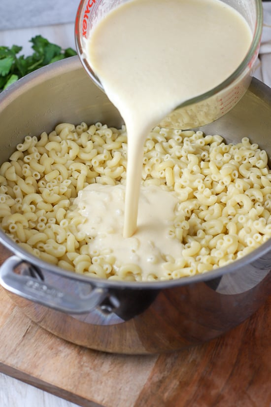 Pot of macaroni pasta with white cheese sauce poured in.