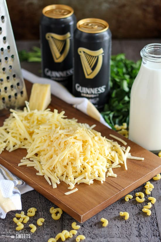 Grated cheese on a wood board with beer and milk in the background.