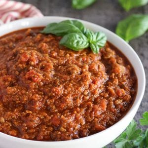 Meat sauce in a white bowl garnished with basil.