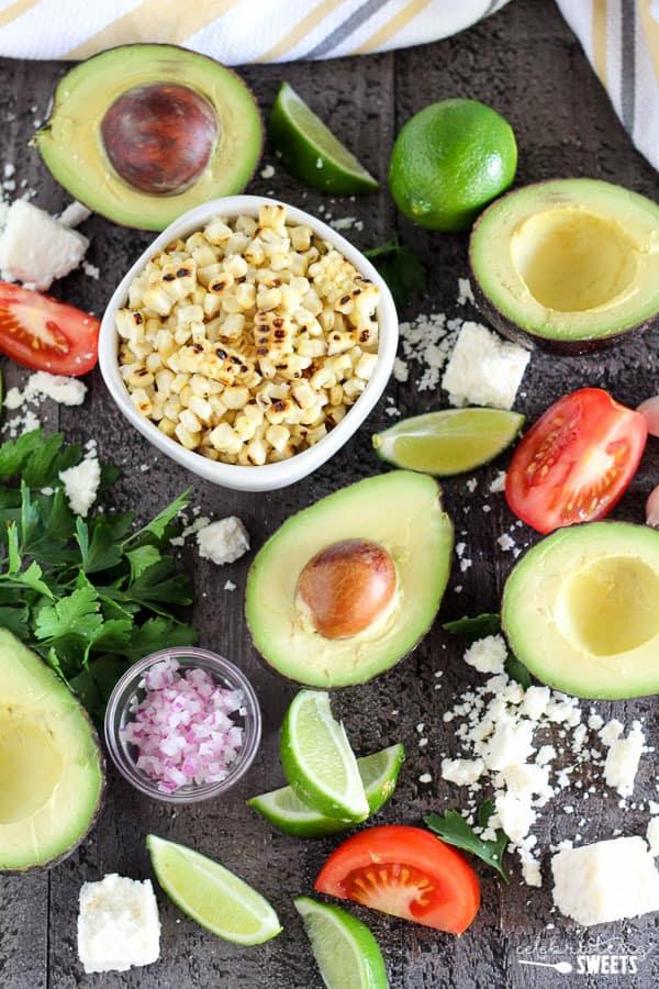 Avocado, corn, tomato, cheese, and lime on a dark board.