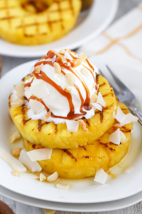 Grilled pineapple on a white plate topped with ice cream.