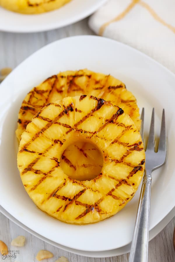 Grilled pineapple slices on a white plate.