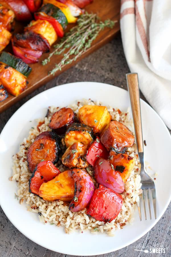 Bowl of rice with grilled sausage and grilled vegetables.