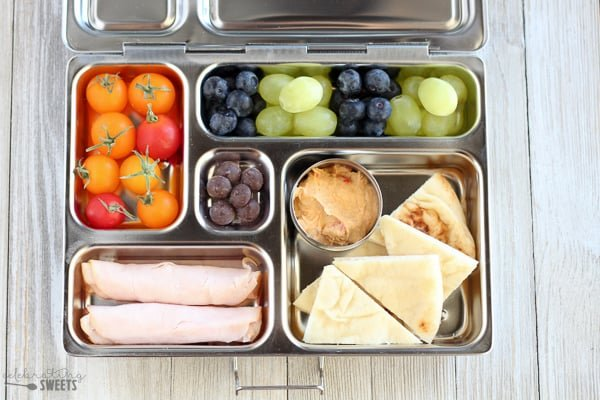 Lunchbox with turkey, pita, hummus and fruit.