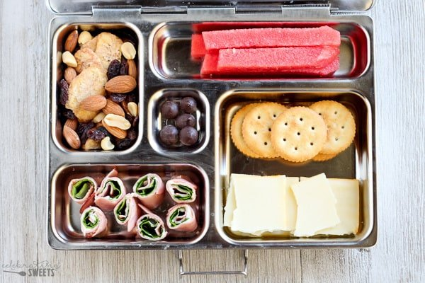 Lunchbox with ham, cheese, crackers, fruit and trail mix.