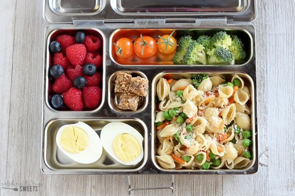 Lunchbox with pasta salad, hard boiled eggs, berries, and veggies.