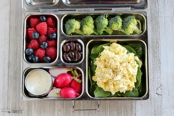 Lunchbox with egg salad, radishes, broccoli and berries.