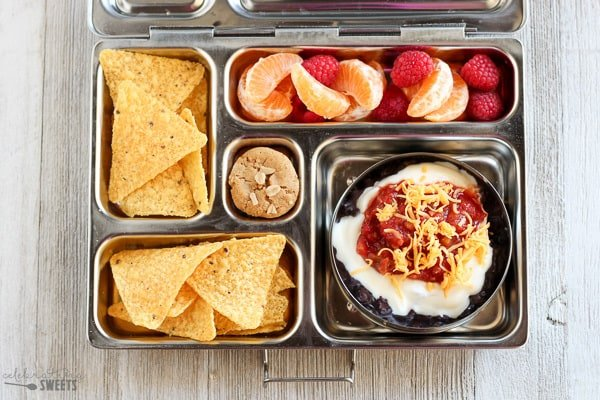 Lunchbox with beans, salsa, tortilla chips and fruit.