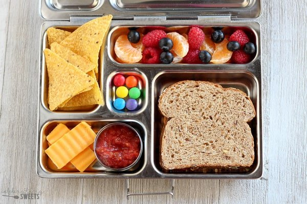 Lunchbox with a sandwich, cheese, chips and salsa, and fruit.