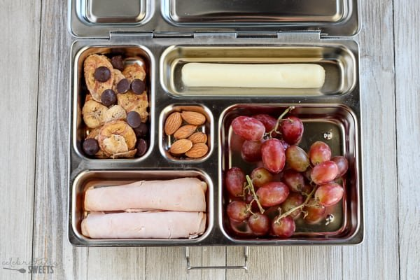 Lunchbox with grapes, turkey, trail mix and string cheese.