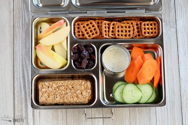 Lunchbox with granola bar, vegetables, apples, pretzels and raisins.