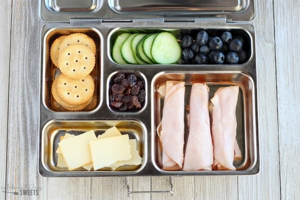 Lunchbox with turkey, cheese, crackers, cucumbrs, blueberries and raisins.