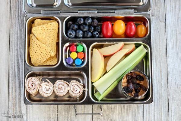 Lunchbox with celery, peanut butter, tortilla pinwheels, chips and fruit.
