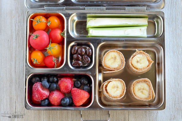 Lunchbox with tortilla roll ups, berries, tomatoes, and celery sticks.