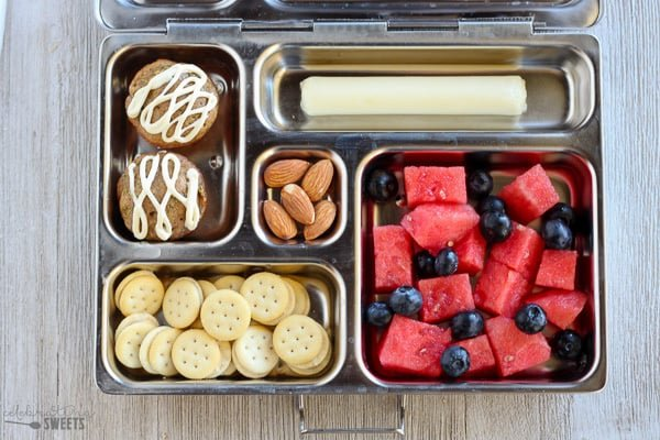 Lunchbox with fruit, crackers, mini muffins, almonds and string cheese.