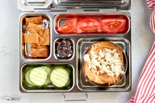 Lunchbox with hummus, cucumbers, crackers, tomatoes and chocolate chips.