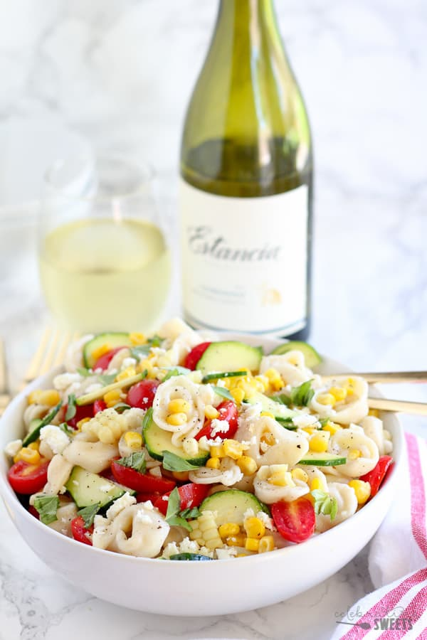 Tortellini Salad in a large white bowl with wine in the background