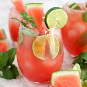Pink Watermelon Mojitos in a glasses garnished with mint, lime, and watermelon.