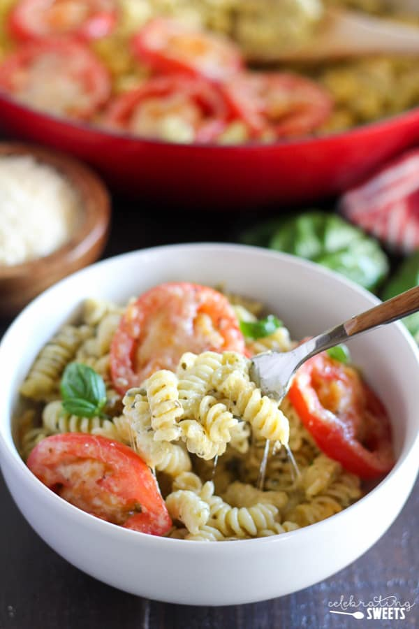 Macaroni and Cheese in a White Bowl topped with Sliced Tomatoes.