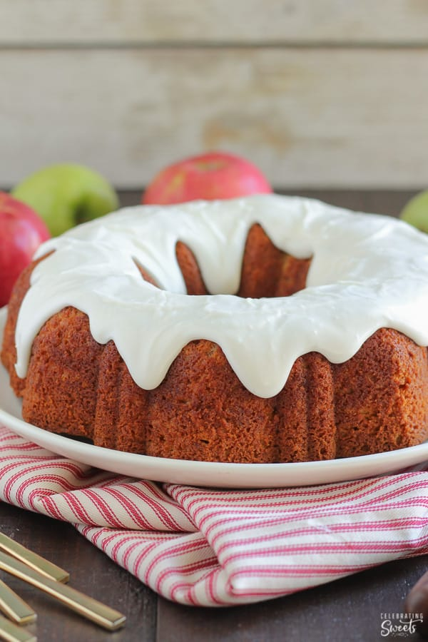 Apple bundt cake topped with cream cheese glaze on a white plate and a red striped napkin.