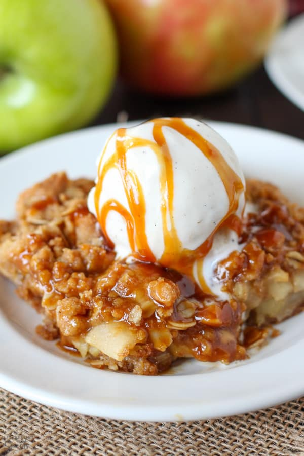 Apple Crumb Bar on a white plate topped with ice cream and caramel sauce.