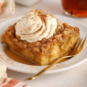 Slice of pumpkin french toast casserole on a white plate topped with whipped cream and cinnamon