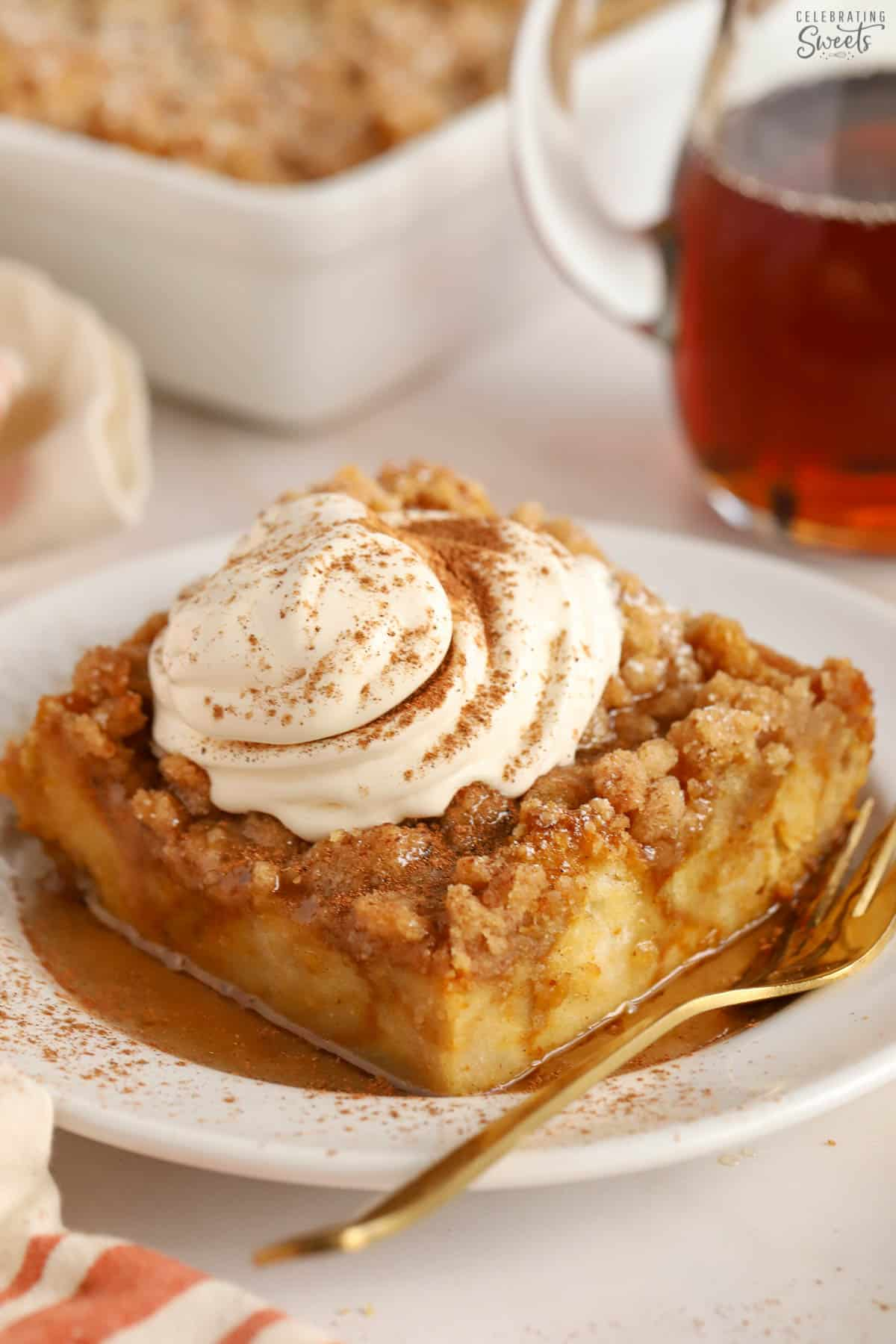 Pumpkin french toast casserole on a white plate topped with whipped cream and cinnamon