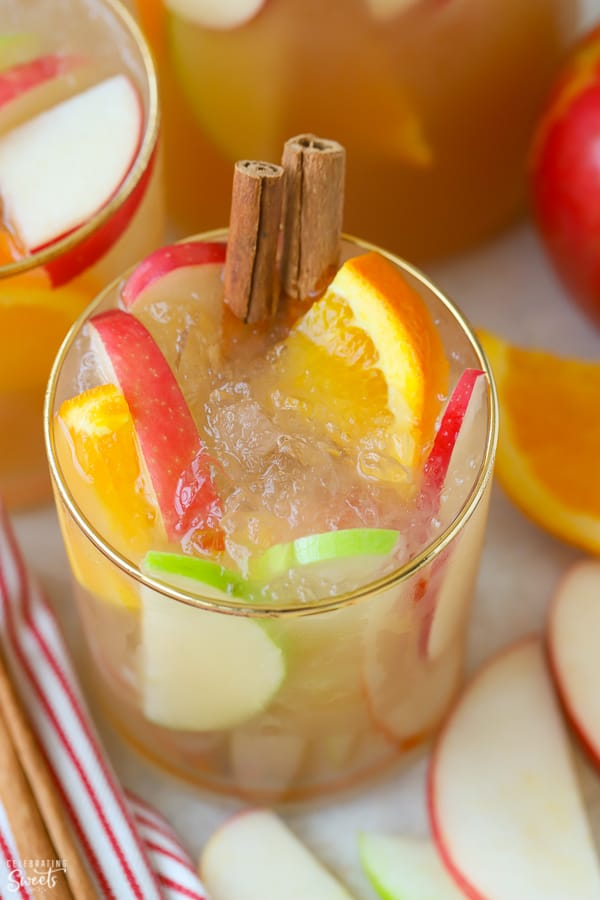 Sangria in a glass garnished with sliced apples, oranges, and cinnamon sticks.