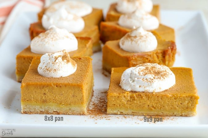 Pumpkin pie bars topped with whipped cream on a white plate.