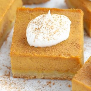 Square slice of pumpkin pie topped with whipped cream.