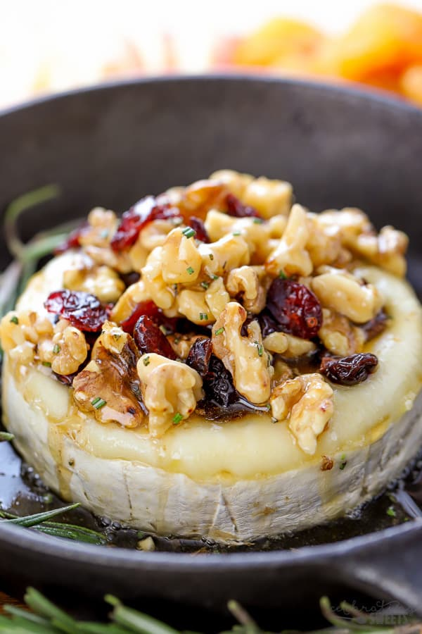 Wheel of brie cheese topped with dried cranberries and walnuts.